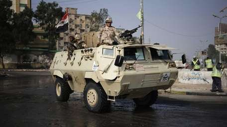 Egyptian Army soldiers stand guard outside the Rabaah