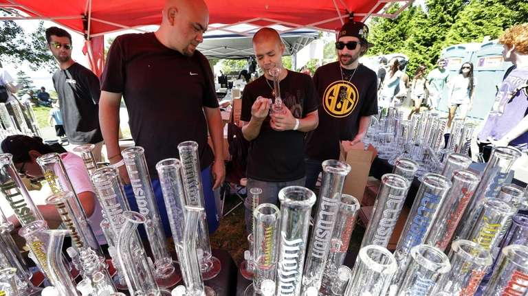 Vendors look over their display of glass bongs