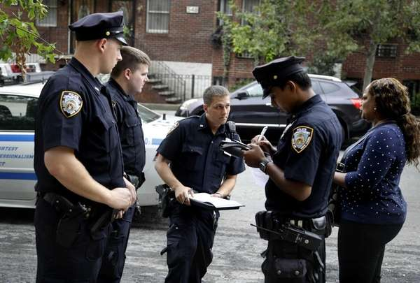 Police officers take a report from a woman