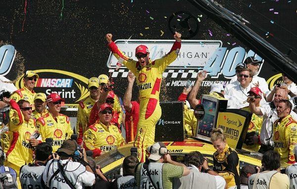 Joey Logano, center, celebrates after winning the NASCAR