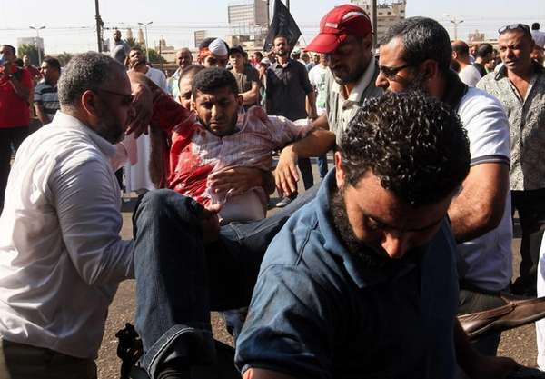 Egyptian demonstrators carry a fellow protester wounded after