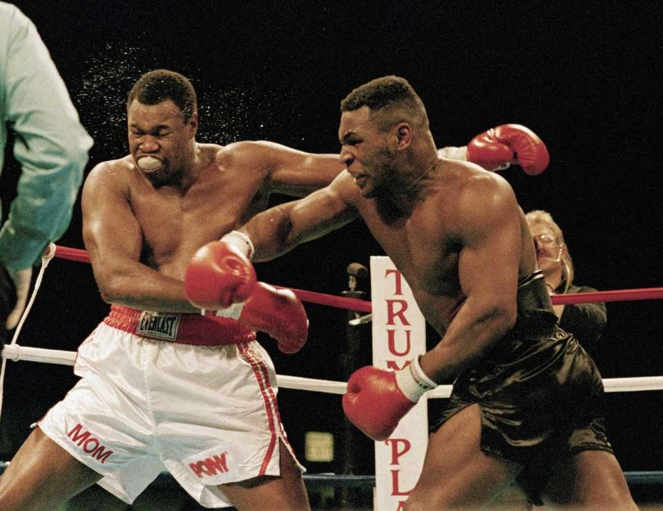 Mike Tyson, right, follows through on a punch