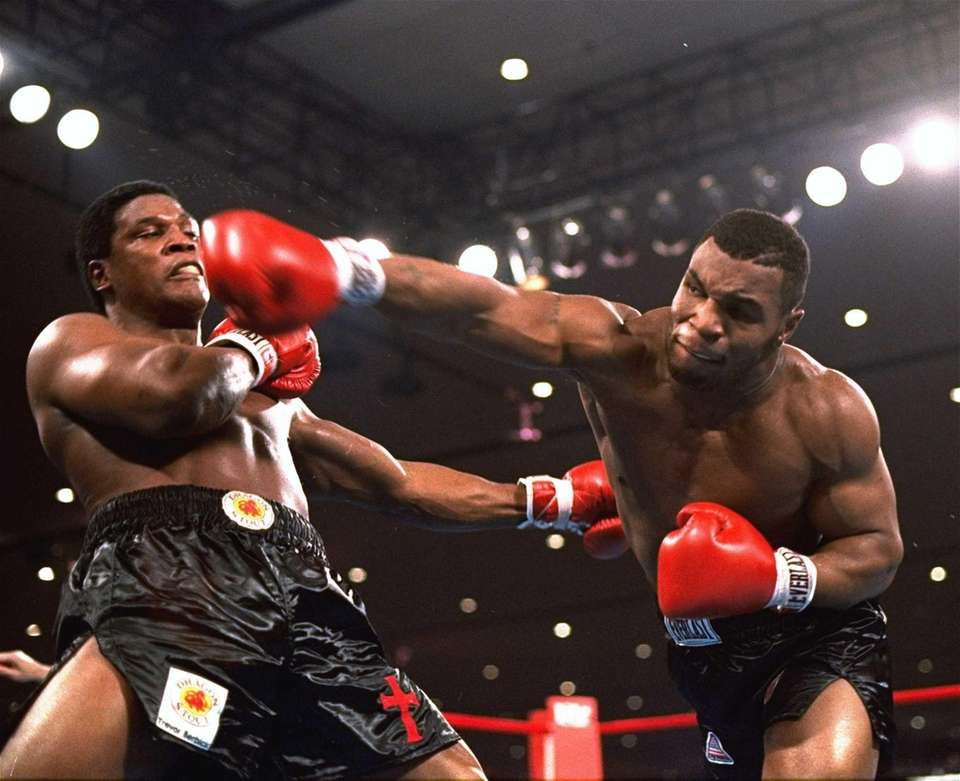 Mike Tyson, right, delivers a blow to Trevor