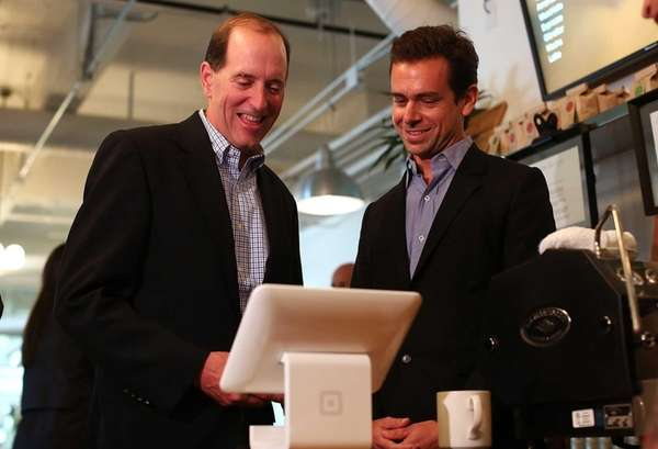 Square CEO Jack Dorsey (R) demonstrates the Square