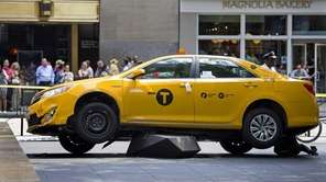 A taxi rests on part of a stone