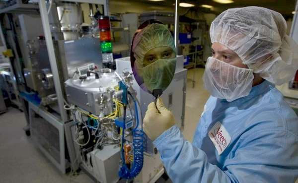 A mechanical engineer holds a data wafer at