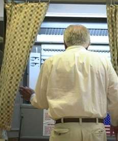 A voter entering a voting booth at Asharoken