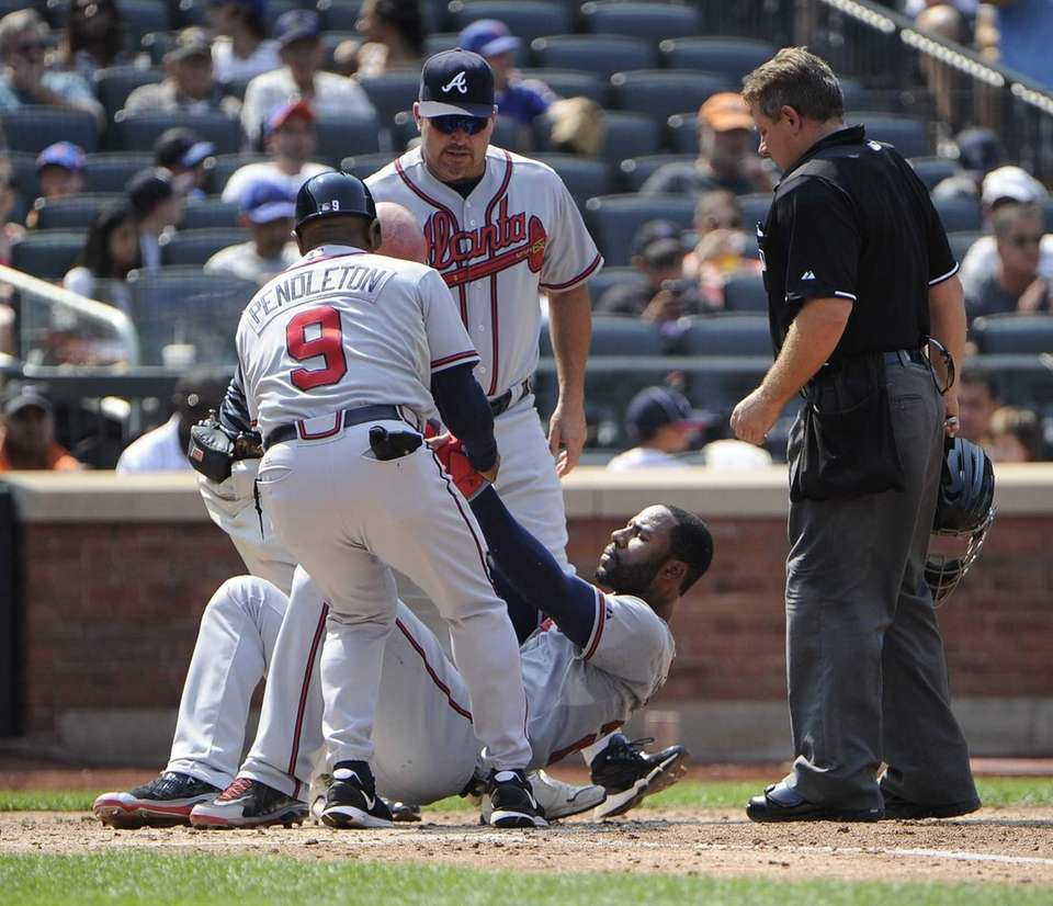 Jason Heyward of the Atlanta Braves is helped