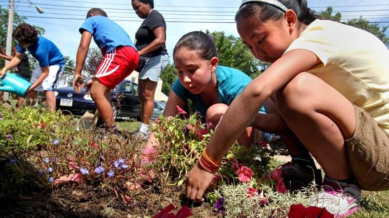 Sisters Mckenzie and Meegan Young plant flowers at