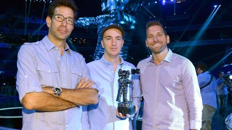 Artist KAWS, designer of the 2013 Moonman, center,