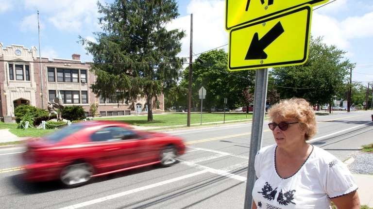 Diane Cheslock, of Eastport, watches as cars speed
