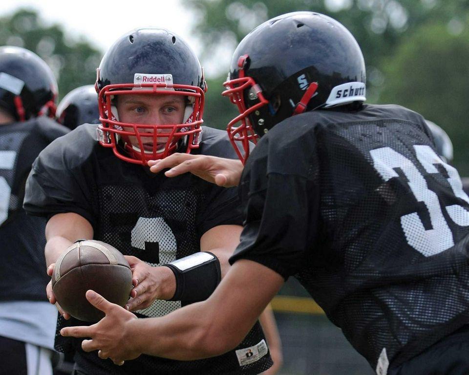Plainedge High School quarterback Nick Frenger, left, hands
