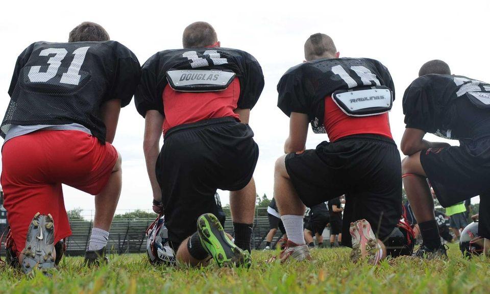Plainedge High School varsity football players kneel down