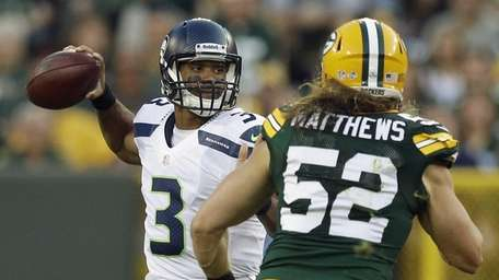 Seattle Seahawks quarterback Russell Wilson tries to avoid