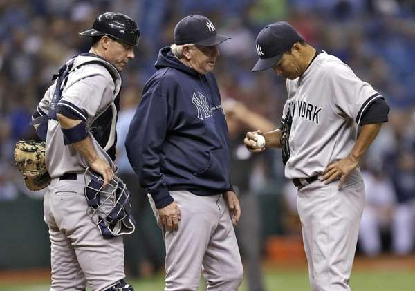 Yankees starting pitcher Hiroki Kuroda, right,reacts as he