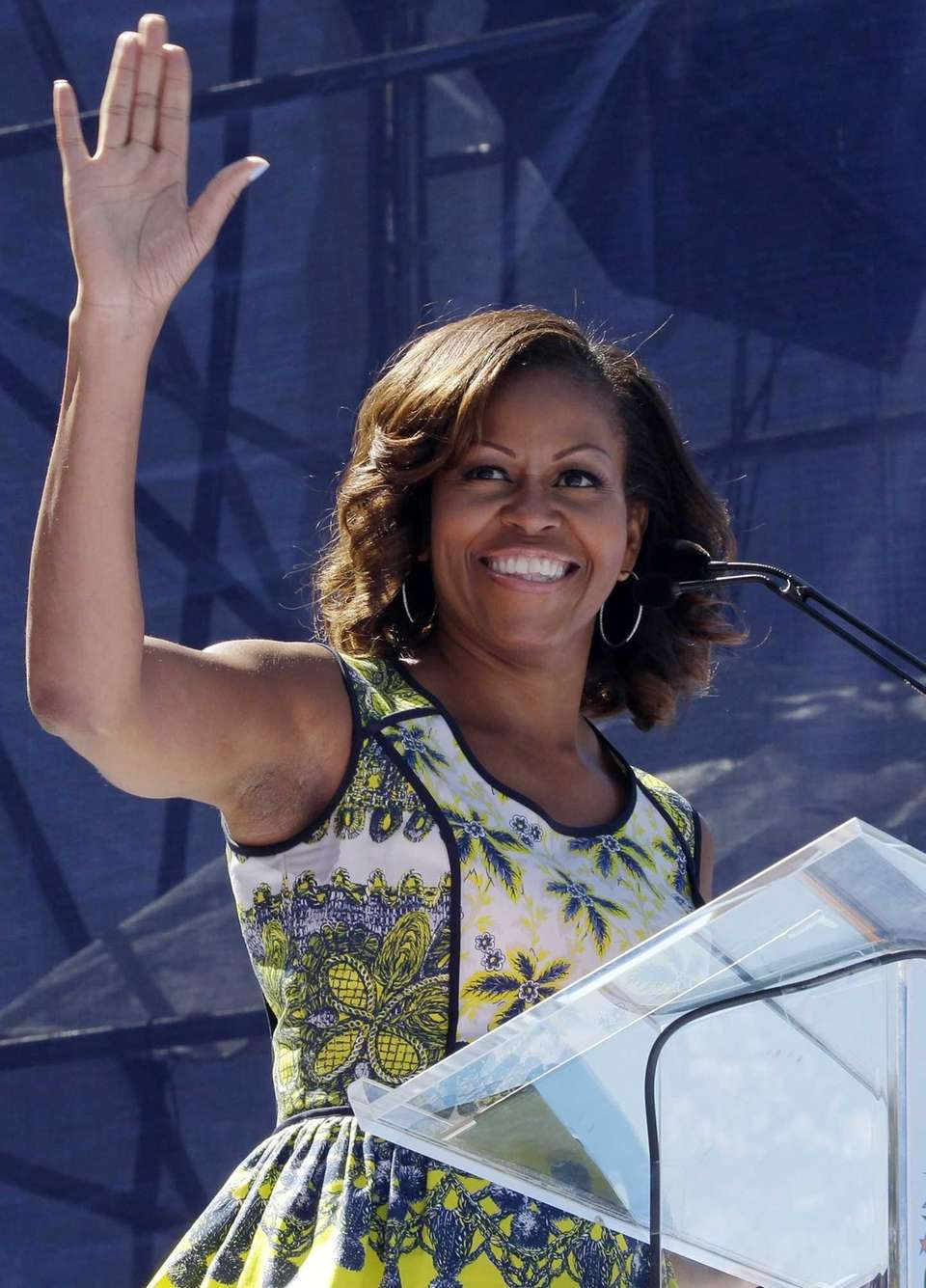 Michelle Obama waves before speaking at the 18th