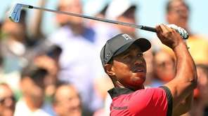 Tiger Woods watches his tee shot on the