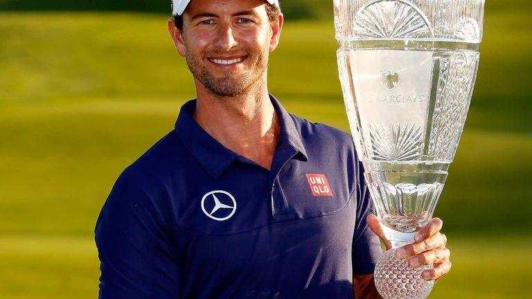 Adam Scott of Australia poses with the trophy