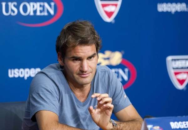 Roger Federer speaks to the media at a