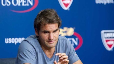 Roger Federer speaks to the media at a