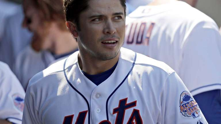 Travis d'Arnaud (15) looks on in the dugout