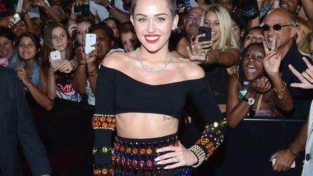 Miley Cyrus, in a gem-covered black crop top