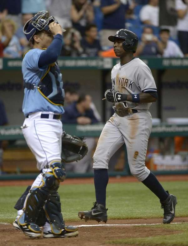 Alfonso Soriano, right, scores from third base on