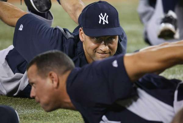 Derek Jeter stretches next to Alex Rodriguez before
