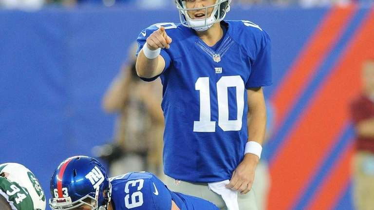 Eli Manning points to the defense during the