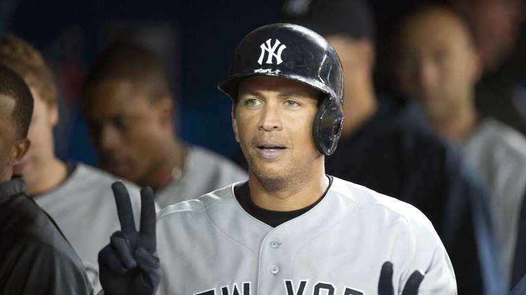 Alex Rodriguez celebrates in the dugout after hitting