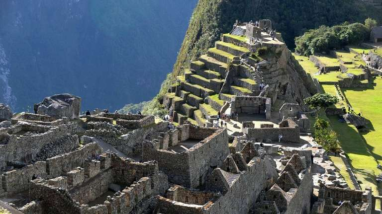 Tourists walk among the ruins of the Machu