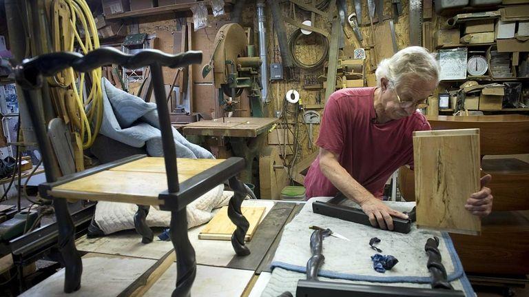Furniture maker David N. Ebner checks a chair