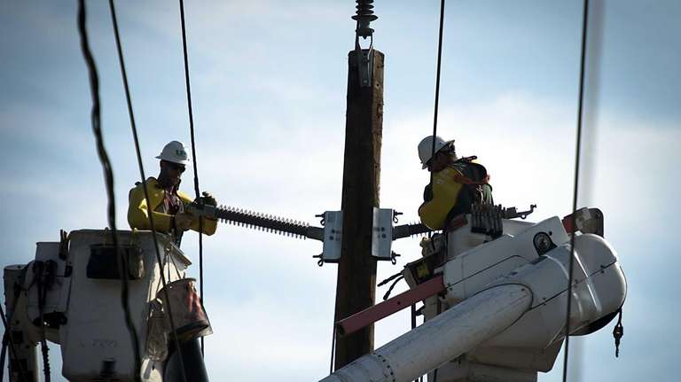 Two linesman work on power lines on Meacham