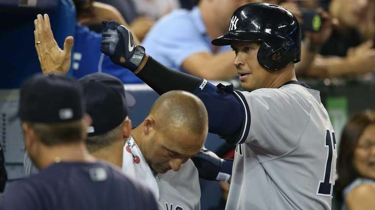 Alex Rodriguez of the Yankees is congratulated by
