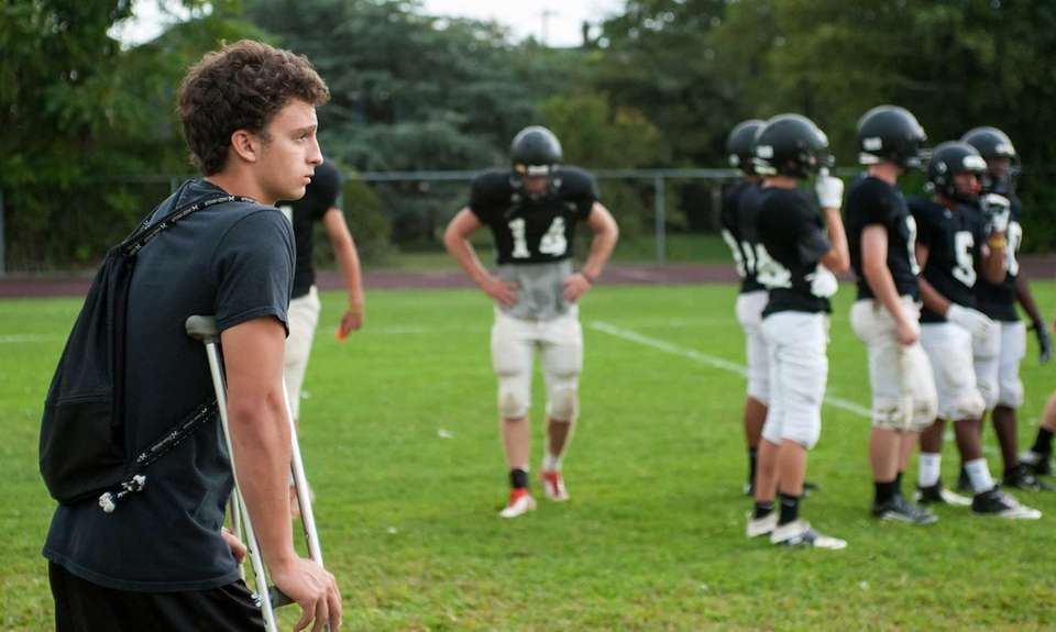 Injured Babylon football player Stephen Cavalieri watches training