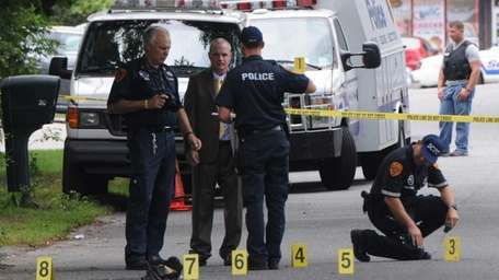 Police investigate the scene of a shooting on