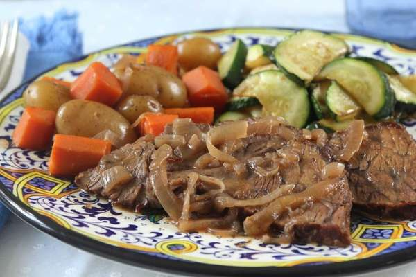 Chuck roast is simmered in red wine, onions,
