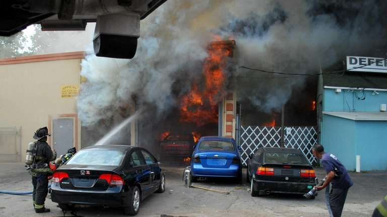 Firefighters battle the fire of an auto body