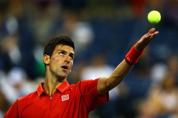 Novak Djokovic of Serbia tosses the ball in