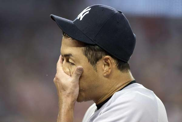 Yankees starting pitcher Hiroki Kuroda wipes his face