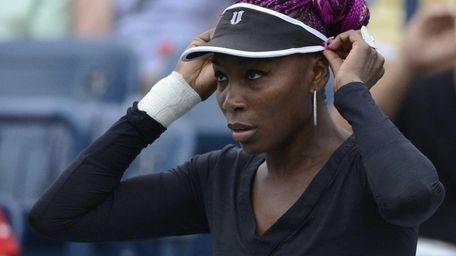 Venus Williams adjusts her visor before her match