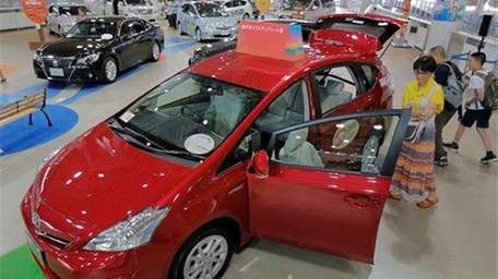 Visitors look at a Toyota Prius hybrid vehicle
