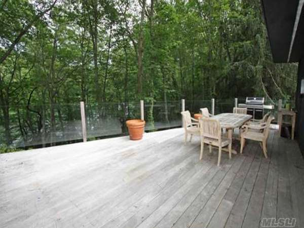 The deck outside a wooded Laurel Hollow property