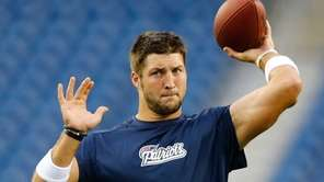 Then-Patriots quarterback Tim Tebow warms up before a