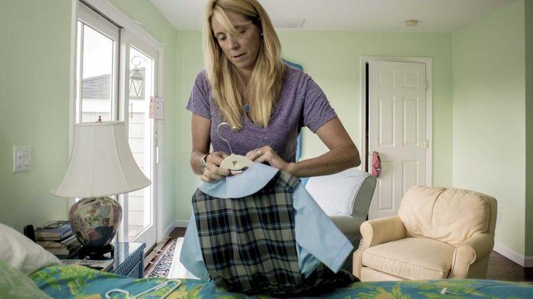 Denise Maier shows her daughter's catholic school uniform