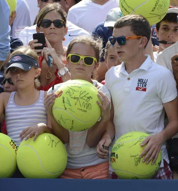 Fans wait court side with large tennis balls