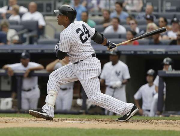 Yankees' Robinson Cano follows through with an RBI