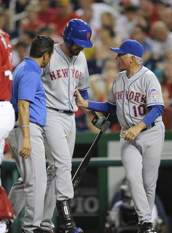 Mets' Ike Davis, center, is tended to by