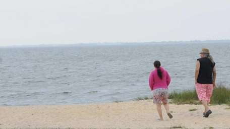 A man and woman walk along the beach