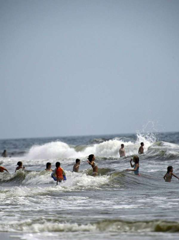 Beachgoers enjoy the water at Robert Moses State